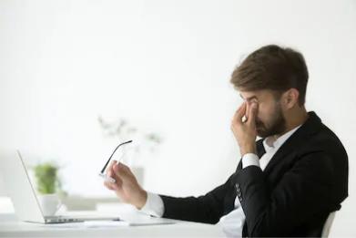 Businessman taking off glasses, fatigued (Shutterstock)